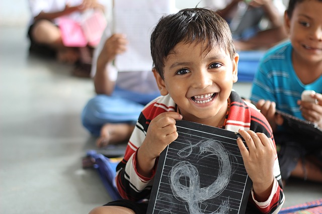 A boy smiles through his first day at school. (Image courtesy: Akshaypatra)